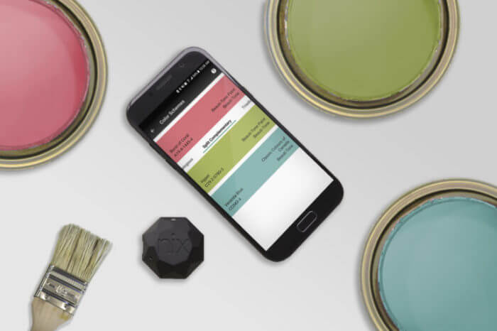 Three Paint cans are opened, showing bright colours. A phone and Nix Mini sit beside the paint cans. The paint colours match the suggested matches from the Nix Mini app.
